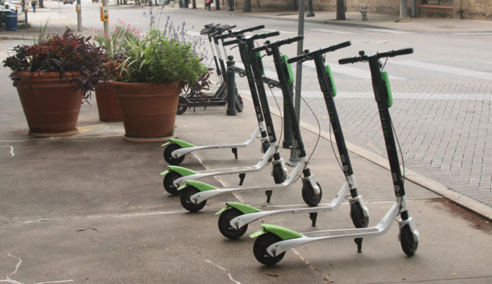 Electric Scooters standing up in a group