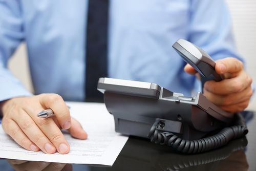 lawyer checking scheduled calls with an office telephone