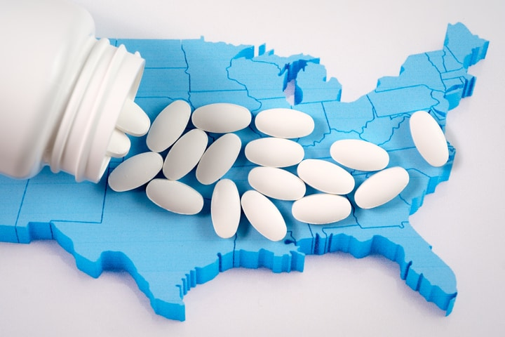 opioid tablets spilled out of container over a US map
