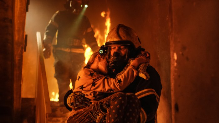 firefighter carrying young girl from burning building in South Carolina